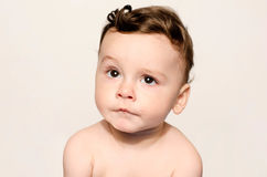 Portrait of a cute baby boy looking up cringing making a funny face. Royalty Free Stock Photography