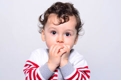 Portrait of a cute baby boy looking up surprised. Adorable one year old child looking away curious with his hands on the mouth. Baby wondering, scared, afraid Stock Image