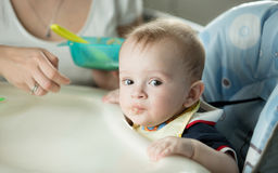 Portrait of cute baby boy sitting in highchair and looking at ca. Closeup portrait of cute baby boy sitting in highchair and looking at camera Royalty Free Stock Image
