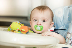 Portrait of cute baby boy with soother waiting for breakfast in Royalty Free Stock Photography