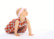 Portrait of cute baby in dress with headband crawls Stock Photos