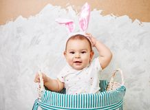Portrait of a cute baby dressed in Easter bunny ears in a basket holds egg happy easter concept stock image