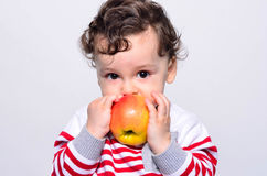 Portrait of a cute baby eating an apple. Royalty Free Stock Images