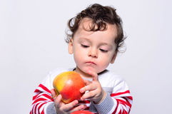 Portrait of a cute baby eating an apple. Royalty Free Stock Photography
