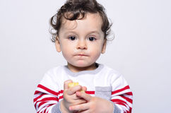 Portrait of a cute baby eating a banana. Stock Images