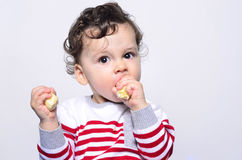 Portrait of a cute baby eating a banana. Royalty Free Stock Photo