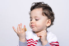 Portrait of a cute baby eating a biscuit looking at the hand. Royalty Free Stock Image