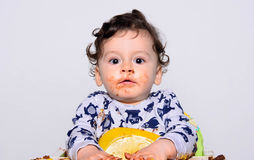Portrait of a cute baby eating cake making a mess. Baby acting surprised trying to hide his mess. Stock Photos