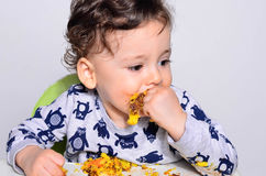 Portrait of a cute baby eating cake making a mess. Royalty Free Stock Photo