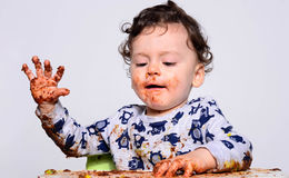 Portrait of a cute baby eating cake making a mess. Royalty Free Stock Images