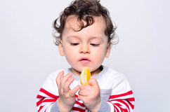 Portrait of a cute baby eating orange. Royalty Free Stock Photography