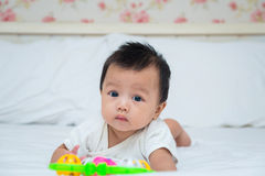 Portrait of cute baby girl on the bed with toy Stock Images