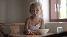 Portrait of cute baby girl eating red cherry tomato