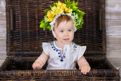Portrait of a cute baby girl on a light background with a wreath of flowers on her head sitting on sofa basket.  Royalty Free Stock Photography