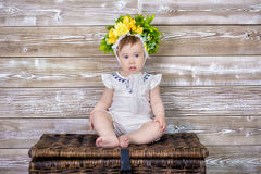 Portrait of a cute baby girl on a light background with a wreath of flowers on her head sitting on sofa basket.  Stock Image