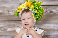 Portrait of a cute baby girl on a light background with a wreath of flowers on her head sitting on sofa basket.  Royalty Free Stock Photo