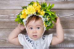 Portrait of a cute baby girl on a light background with a wreath of flowers on her head sitting on sofa basket Stock Photo