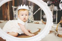 Portrait of a cute baby girl with paper crown. Portrait of a cute baby girl in white dress with a paper crown in the frame Stock Image