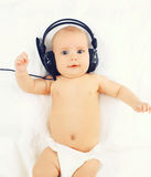Portrait of cute baby listens to music in headphones lying Royalty Free Stock Images