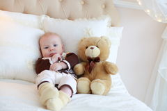 Portrait of a cute baby lying on the white bed Stock Photography