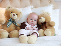 Portrait of a cute baby lying on the white bed Stock Image
