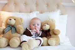 Portrait of a cute baby lying on the white bed Stock Photo