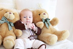 Portrait of a cute baby lying on the white bed with toy friends Stock Photo