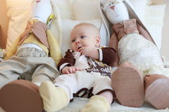 Portrait of a cute baby lying on the white bed with toy friends Stock Photos