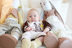 Portrait of a cute baby lying on the white bed with toy friends Royalty Free Stock Images
