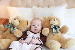 Portrait of a cute baby lying on the white bed with toy friends Royalty Free Stock Image