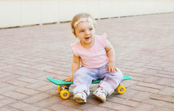 Portrait of cute baby sitting on the skateboard outdoors Stock Photos