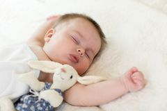 Portrait of cute baby sleeping on bedspread, close up view stock images