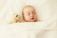 Portrait of cute baby sleeping together with teddy bear toy Royalty Free Stock Image