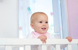 Portrait of a cute baby smiling in crib Stock Images