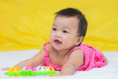 Portrait of cute baby smiling girl on the bed with toy Stock Photos