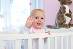 Portrait of a cute baby smiling and waving hello Stock Photos