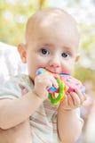 Portrait of a cute baby sucks rattle Stock Photo