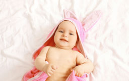 Portrait of cute baby in towel lying on the bed at home Stock Photography