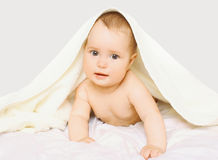 Portrait of cute baby under towel on the bed Royalty Free Stock Photos