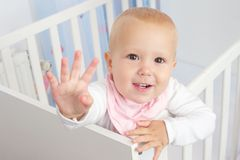 Portrait of a cute baby waving hello and smiling from crib Royalty Free Stock Image