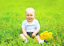 Portrait of cute baby with yellow dandelion flowers sitting on t. He grass in sunny summer day Royalty Free Stock Photos