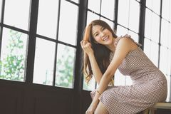 Portrait of cute and beautiful Asian girl smiling in coffee shop or modern office with copy space. Happy people, modern lifestyle Stock Image