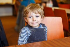 Portrait of cute beautiful toddler kid boy waiting in canteen of kindergarten for meal. Healthy happy child looking at royalty free stock image
