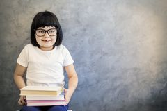 Cute black hair little girl with glasses holding books by the wa Royalty Free Stock Images