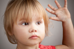 Portrait of cute blond baby girl with hand up gesture Stock Photo