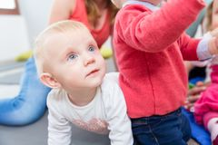 Portrait of a cute blond baby girl playing with colorful toys royalty free stock photos
