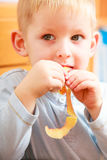 Portrait of cute blond child boy kid eating apple peel. At home. Royalty Free Stock Images