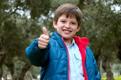 Portrait of a cute blond-haired boy, thumbs up and smile stock image