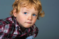 Portrait of cute blond toddler with blue eyes looking thoughtful Stock Photo