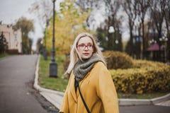 Portrait of cute blonde in autumn park stock image